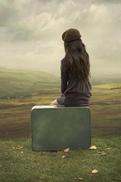 Robin Macmillan Teenage girl in purple sweater sitting on suitcase by hills