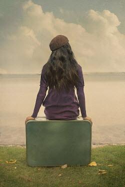 Robin Macmillan Teenage girl in purple sweater sitting on suitcase by lake