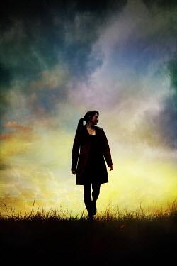 Silas Manhood BRUNETTE WOMAN WALKING IN FIELD AT SUNSET Women