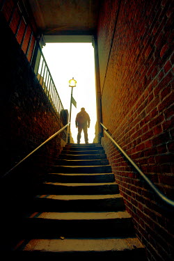 Silas Manhood SILHOUETTED MAN ON STEPS OF BRICK BUILDING Men