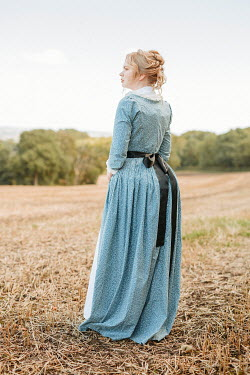 Shelley Richmond Young woman in blue dress standing in field