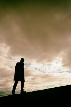 Tim Robinson Silhouette of man in hat and coat at sunset