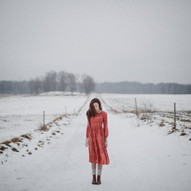 Dasha Pears Young woman in red dress on snowy rural road