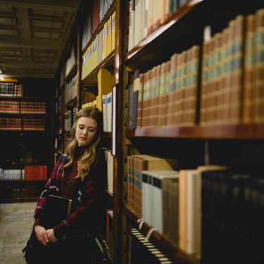 Dasha Pears Young woman leaning on bookshelves in library