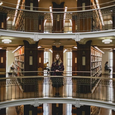 Dasha Pears Young woman standing by railing in library