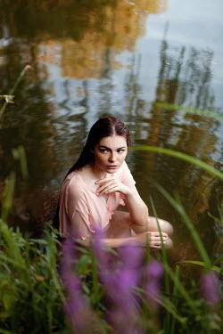 Elena Alferova Young woman in pink dress sitting in river