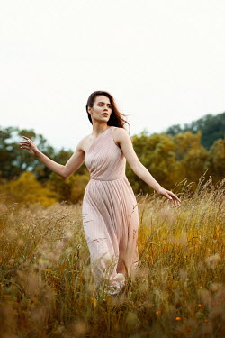 Elena Alferova Young woman in pink dress running in field
