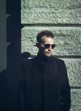Mark Owen Young man in black coat and sunglasses by wall