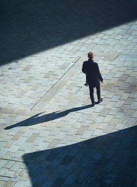 Mark Owen Man in black coat walking in public square