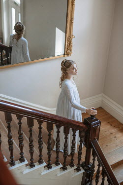 Shelley Richmond Young woman in Victorian night dress on staircase