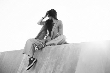 Elena Alferova WOMAN IN SUIT AND SNEAKERS ON WALL OUTDOORS Women