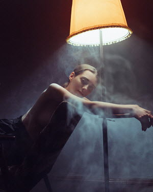 Ihor Ustynskyi BRUNETTE WOMAN SITTING UNDER LAMP WITH SMOKE Women