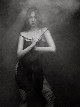 Ihor Ustynskyi WOMAN WITH DRESS AND FISHNET TIGHTS IN SMOKEY ROOM Women