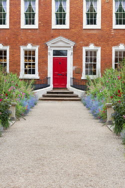 Lee Avison gravel driveway leading to red front door of a georgian townhouse in summer