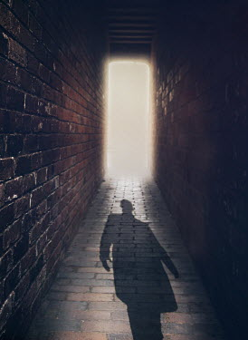 Mark Owen SHADOW OF MAN ON FLOOR OF BRICK PASSAGEWAY Men