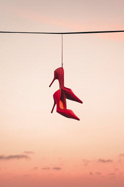 Evelina Kremsdorf Red high heels hanging from wire at sunset