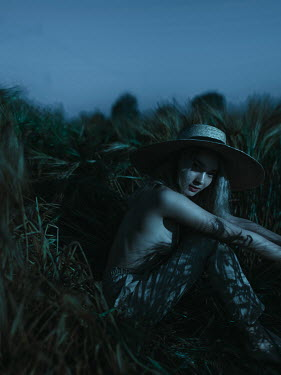 Ihor Ustynskyi Topless woman in straw hat sitting in grass at night