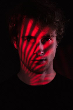 Magdalena Russocka man's face in striped shadow and red light