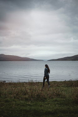 Shelley Richmond Young woman in leather jacket walking in grass by lake
