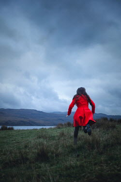 Shelley Richmond Young woman in red coat running in field