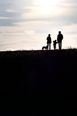 Ute Klaphake Silhouette of family with dog on hill