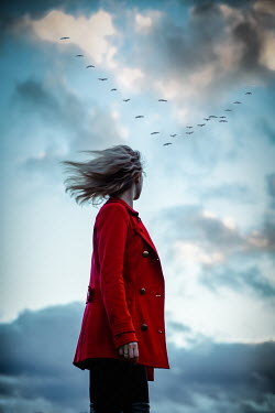 Natasza Fiedotjew Blonde woman in red coat watching flock of birds