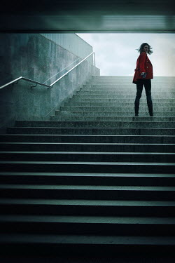 Natasza Fiedotjew Woman in red coat with gun on underground stairs