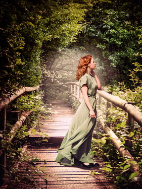 Elisabeth Ansley Young woman in green dress on wooden bridge