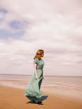 Elisabeth Ansley Young woman in green dress walking on beach