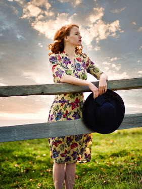 Elisabeth Ansley Young woman in floral dress leaning on fence at sunset