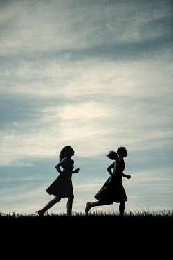 Magdalena Russocka two girls running in field at dusk Women