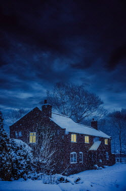 Nic Skerten House with lit windows under snow at night