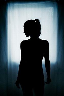 Nic Skerten Silhouette of naked woman by window