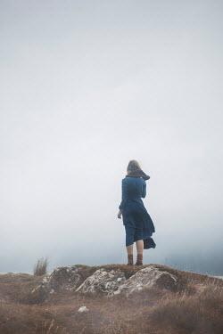 Shelley Richmond Young woman in blue dress standing on rock under fog