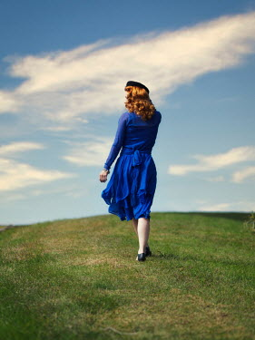 Elisabeth Ansley Woman in blue dress walking on hill