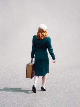 Elisabeth Ansley Woman in green dress walking with suitcase