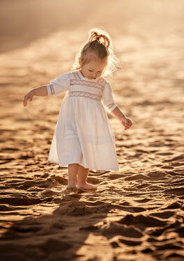 Lilia Alvarado Girl in white dress walking on beach at sunset