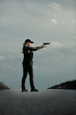 Magdalena Russocka modern woman aiming with gun standing on road
