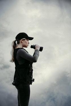 Magdalena Russocka modern woman holding binoculars