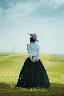 Ildiko Neer Victorian woman holding book in meadow