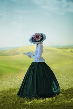 Ildiko Neer Victorian woman reading book in meadow