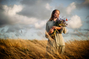 Klaudia Rataj Young woman holding bouquet in field