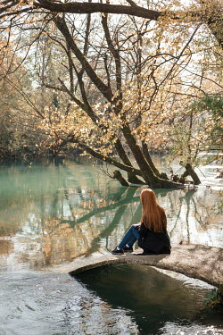 Nina Masic Young woman sitting by river