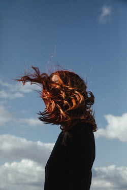 Matilda Delves WOMAN WITH RED HAIR FLOWING IN WIND OUTDOORS Women