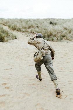 Matilda Delves Soldier running on sand dunes
