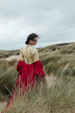 Matilda Delves Young woman in Victorian dress on sand dunes