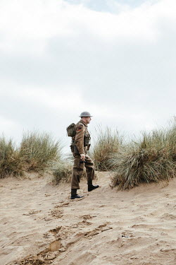 Matilda Delves WWI soldier walking on sand dunes