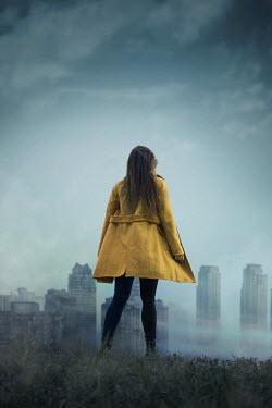Ildiko Neer WOMAN IN FIELD WATCHING FOGGY CITYSCAPE Women