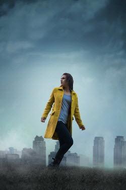 Ildiko Neer Modern woman walking in field with skyscrapers