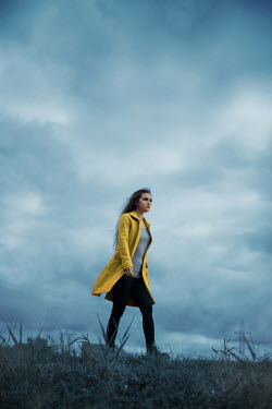 Ildiko Neer Modern woman in yellow coat walking in field